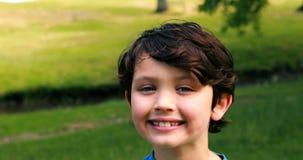 微笑的男孩画象在公园 股票视频