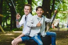 微笑的男孩获得乐趣在操场 使用户外在夏天的孩子 乘坐在摇摆的少年外面 免版税图库摄影