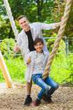微笑的男孩获得乐趣在操场 使用户外在夏天的孩子 乘坐在摇摆的少年外面 库存照片