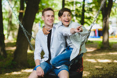 微笑的男孩获得乐趣在操场 使用户外在夏天的孩子 乘坐在摇摆的少年外面 图库摄影