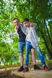 微笑的男孩获得乐趣在操场 使用户外在夏天的孩子 乘坐在摇摆的少年外面 库存图片