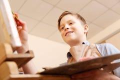 微笑的男孩表现出喜悦用学校 免版税库存图片