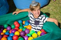 微笑的男孩画象球水池的 图库摄影