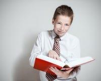 微笑的男小学生与读一本大红色书 免版税库存图片