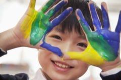 微笑的男小学生手指画法,关闭画象在手上 免版税库存图片