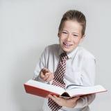 微笑的男小学生读一本大红色书 库存图片