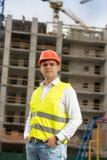 微笑的男性工程师画象摆在反对建筑工地的安全帽的 库存图片