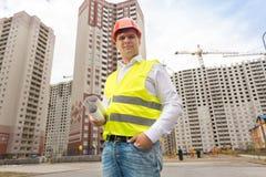 微笑的男性工程师画象站立与图纸的安全帽的反对修造建设中 免版税库存照片