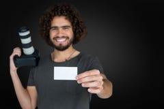 微笑的男性摄影师画象的综合图象显示卡片的,当拿着照相机时 库存照片