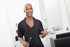 微笑的男性美发师藏品剪和发刷 免版税库存图片