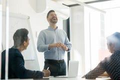微笑的男性赠送者在办公室嘲笑新闻发布会 免版税库存图片