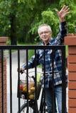 微笑的男性骑自行车者挥动 免版税库存图片