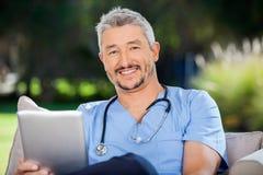 微笑的男性医生With Tablet Computer 免版税图库摄影