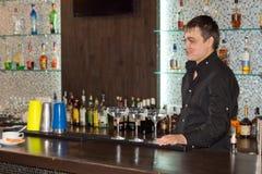 微笑的男服务员服务酒客鸡尾酒 库存照片