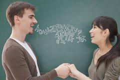 微笑的男老师和学生画象在握手的黑板前面 图库摄影