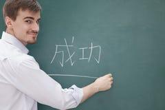 微笑的男老师画象在黑板文字,汉字前面的 免版税库存图片