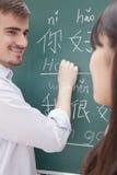 微笑的男老师画象有学生的在黑板文字前面 免版税库存照片
