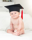 微笑的男婴被定调子的画象看毕业的帽子的  免版税库存图片