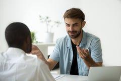 微笑的白种人工作者谈话与黑人同事在办公室 免版税图库摄影