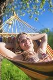 微笑的白种人白肤金发的夫人Resting画象在小丘在春天 免版税库存照片