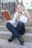 微笑的白种人白肤金发的女性画象有走下去坐台阶户外和读的书的 免版税图库摄影