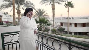 微笑的白种人资深妇女谈话在一个旅馆大阳台的一个智能手机在一件白色特里长袍在一种热带手段 影视素材