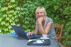 微笑的白肤金发的中部在室外办公室变老了妇女 免版税图库摄影