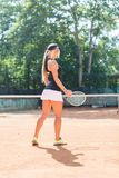 微笑的白肤金发的女子网球员充分的身体画象行动的在室外的网球场 免版税库存图片