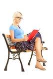 微笑的白肤金发的女学生坐长凳和阅读书 免版税库存照片