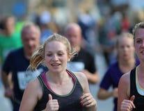 微笑的白肤金发的妇女赛跑 库存照片