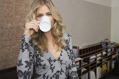 微笑的白肤金发的妇女饮用的咖啡在办公室 免版税库存图片