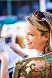 微笑的白肤金发的妇女读书报纸户外 免版税图库摄影