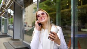 微笑的白肤金发的有夫之妇谈话在城市街道上的手机 股票视频