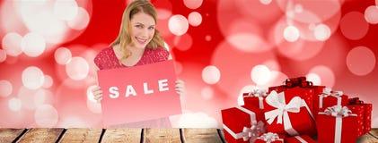 微笑的白肤金发的陈列的综合图象一张红色销售海报 免版税库存照片