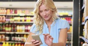 微笑的白肤金发的购物和使用智能手机