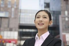 微笑的确信的年轻女实业家画象,户外有修造的外部在背景在北京,中国 免版税库存图片