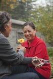 给微笑的祖母一朵花的祖父在庭院里 免版税库存图片