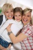 微笑的祖母和母亲拥抱的小女孩 免版税库存照片