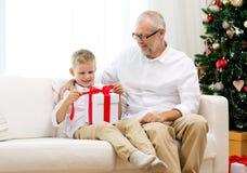 微笑的祖父和孙子有礼物盒的 免版税库存图片