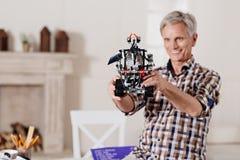 微笑的祖父审查的玩具机器人 免版税库存照片