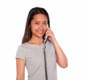 微笑的种族少妇交谈在电话 图库摄影