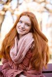 微笑的红头发人妇女坐长凳户外 免版税库存照片