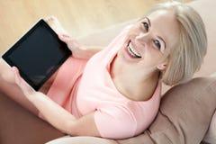 微笑的美丽的中年妇女坐有一种片剂的长沙发,就新的想法而论 库存照片