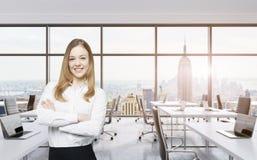 微笑的美丽的企业夫人用发怒手在一个现代全景办公室站立在纽约 曼哈顿日落视图 库存照片