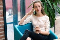 微笑的美丽的女孩谈话在电话和饮用的鸡尾酒在咖啡馆 美丽的微笑的妇女画象坐a 库存照片