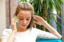 微笑的美丽的女孩谈话在电话和饮用的鸡尾酒在咖啡馆 美丽的纵向微笑的妇女 免版税库存图片