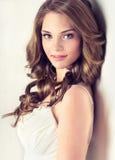 微笑的美丽的女孩,有一种典雅的发型的棕色头发,头发挥动,卷曲 免版税库存图片