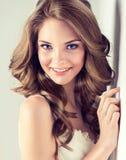 微笑的美丽的女孩,有一种典雅的发型的棕色头发,头发挥动,卷曲 免版税库存照片