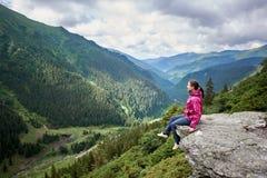微笑的美丽的女性游人坐岩石渐近绿色象草的倾斜和山赞赏的激动人心的景色  库存图片