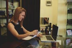 微笑的美丽的妇女顾问重写在纸张文件的价格从便携式计算机,当站立在商店出纳员柜台时 免版税图库摄影